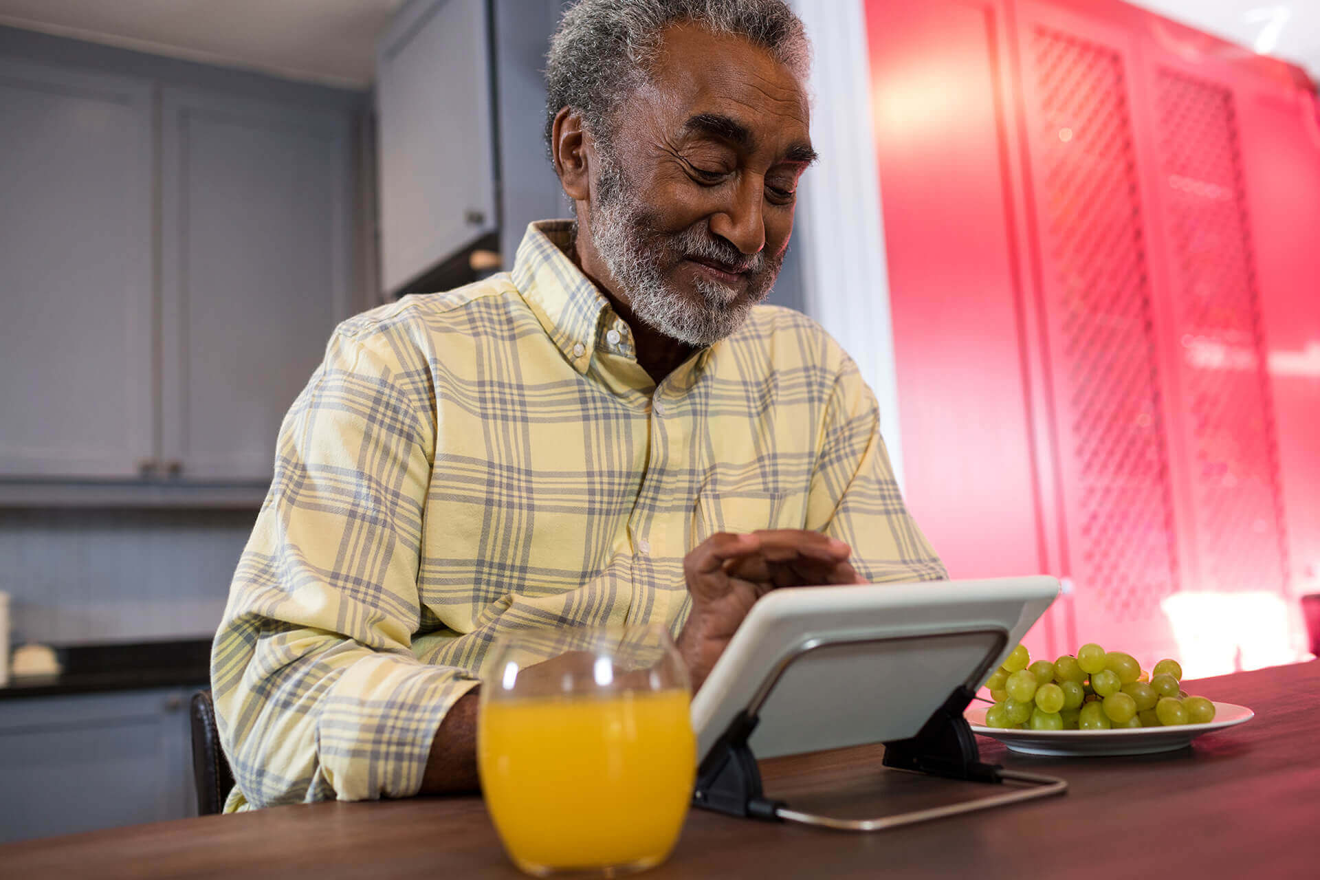 happy senior man using tablet computer in kitchen SUXG8R9 1