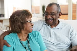 senior black couple sitting at home smiling at eac ZV3PTQJ