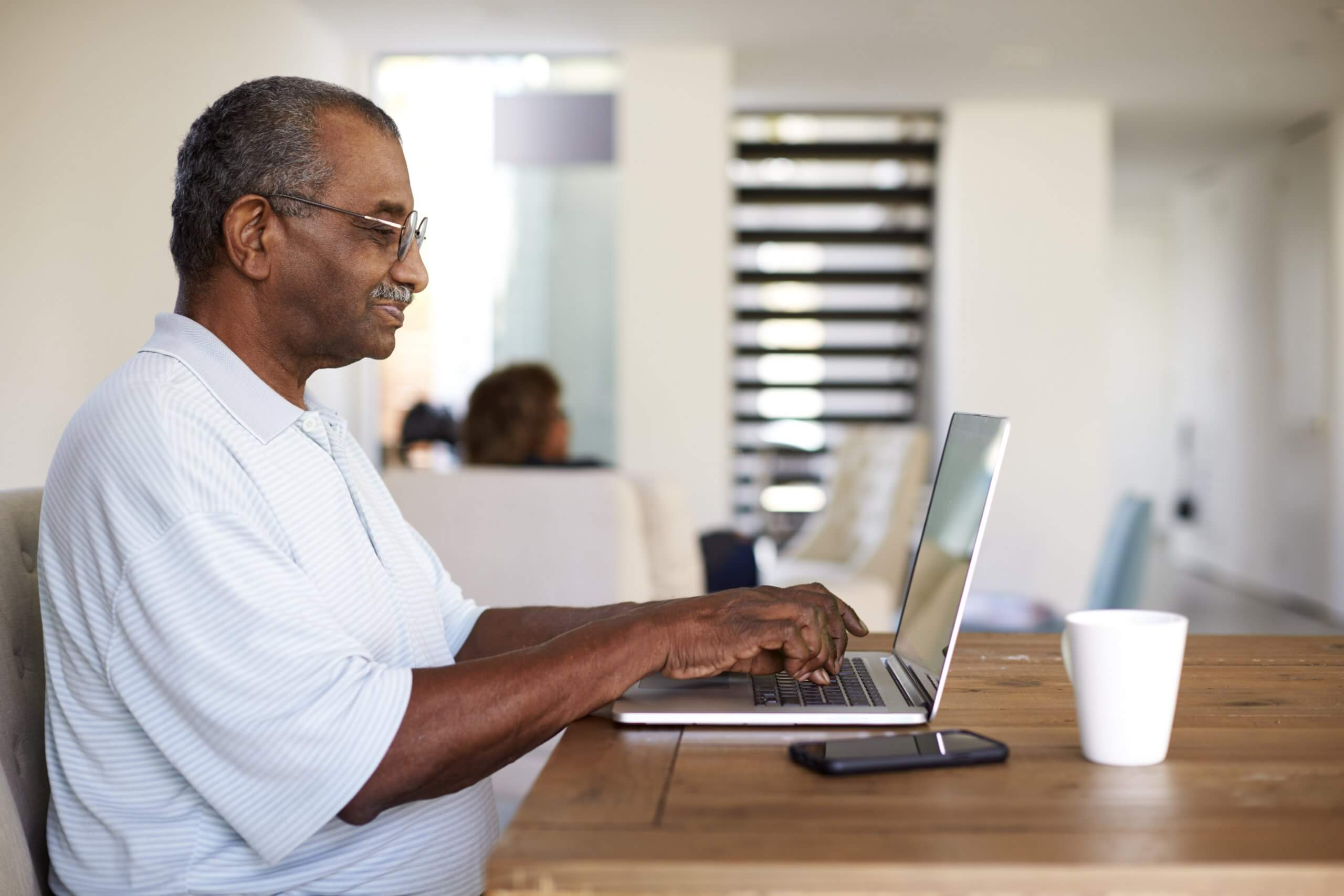 senior black man sitting at the table using a lapt QGBH2WD 1
