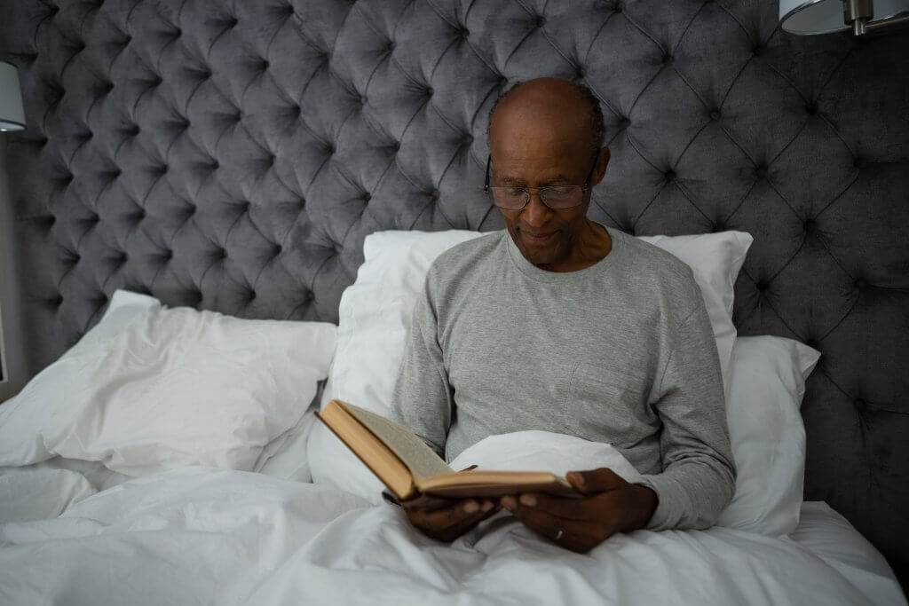 senior man reading book while sitting on bed Y2QH9VB